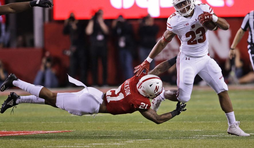 Wisconsin running back Jonathan Taylor (23) runs past a tackle attempt by Nebraska defensive back Lamar Jackson (21) during the first half of an NCAA college football game in Lincoln, Neb., Saturday, Oct. 7, 2017. (AP Photo/Nati Harnik)