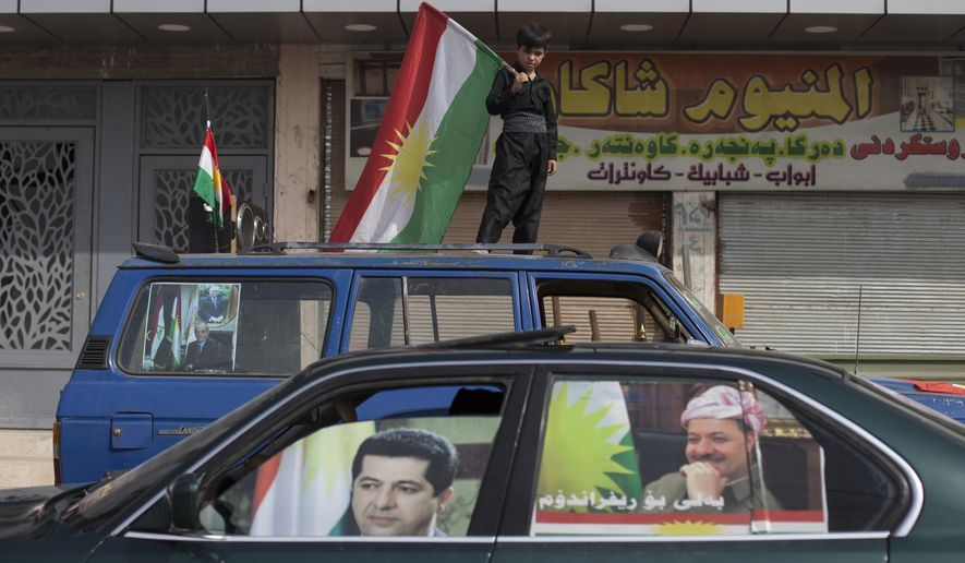 FILE - In this, Sept. 25, 2017 file photo, a boy carries a Kurdish flag on top of a car with pictures of Kurdish president Masoud Barzani and his son Masrour on the windows, in the disputed city of Kirkuk, Iraq.  The office of Iraq's parliament speaker says Salim Jabouri is traveling to the country's Kurdish region to meet with Barzani, Sundaay, Oct. 8, 2017. The move comes in the wake of the Kurdish regional vote for independence in a controversial referendum two weeks ago. (AP Photo/Bram Janssen, File)