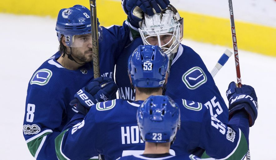 Vancouver Canucks' goalie Jacob Markstrom, back right, of Sweden, Chris Tanev (8) and Bo Horvat (53) celebrate after defeating the Edmonton Oilers 3-2 during the third period of an NHL hockey game in Vancouver, British Columbia, Saturday, Oct. 7, 2017. (Darryl Dyck/The Canadian Press via AP)