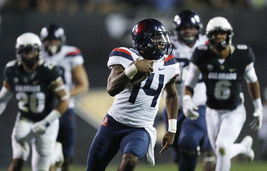 Arizona quarterback Khalil Tate, front, runs for a touchdown past Colorado linebacker Drew Lewis, back left, and defensive back Evan Worthington in the second half of an NCAA college football game Saturday, Oct. 7, 2017, in Boulder, Colo. Arizona won 45-42. (AP Photo/David Zalubowski)