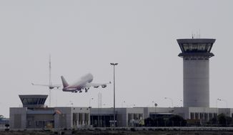 "An aircraft takes off from Larnaca airport past the control tower, right, Saturday, Oct. 7, 2017, at the southern coastal city of Larnaca, Cyprus. A report by Europe's air safety agency says rival air traffic control centers giving flight instructions to aircraft flying through the island's airspace are compromising air travel safety by creating ""confusion and misunderstanding"" among pilots. (AP Photo/Petros Karadjias)"