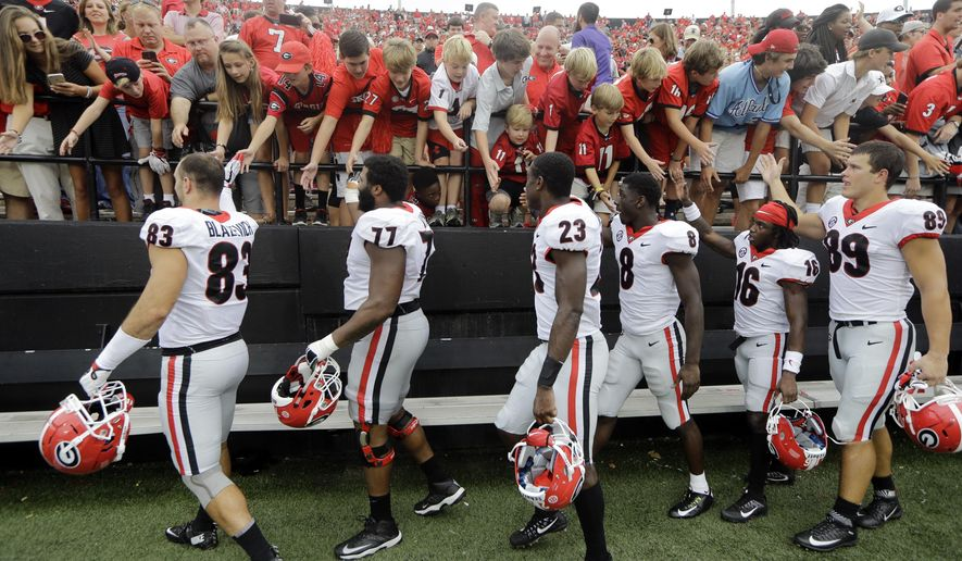 Georgia players slap hands with fans after beating Vanderbilt 45-14 in an NCAA college football game Saturday, Oct. 7, 2017, in Nashville, Tenn. (AP Photo/Mark Humphrey)
