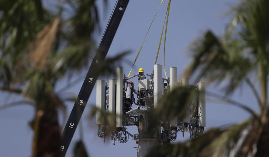 In this Friday, Sept. 29, 2017 photo, workers make repairs to a cell tower, in Port Aransas, Texas. The tower was damaged during Hurricane Harvey. Tourists are expected to stay away through the holidays, and even the possibility of getting back to business by spring break looks bleak. (AP Photo/Eric Gay)