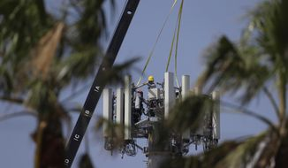 In this Friday, Sept. 29, 2017 photo, workers make repairs to a cell tower, in Port Aransas, Texas. (AP Photo/Eric Gay) **FILE**