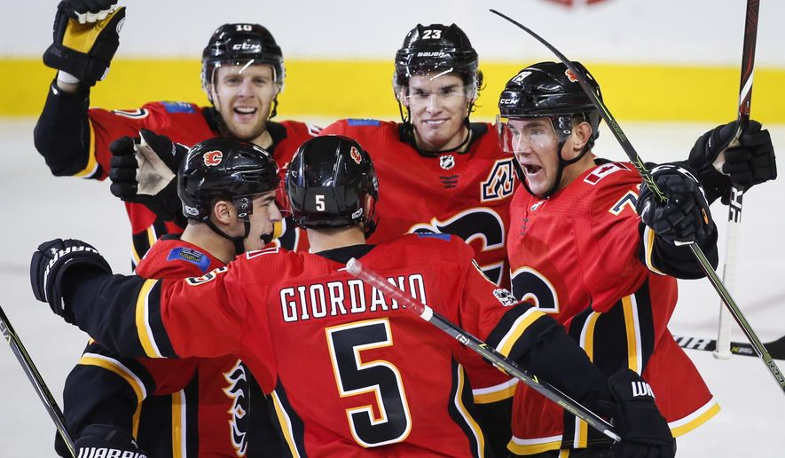 Calgary Flames' Micheal Ferland, right, celebrates his goal with teammates against the Winnipeg Jets during the second period of an NHL hockey game in Calgary, Alberta, Saturday, Oct. 7, 2017. (Jeff McIntosh/The Canadian Press via AP)