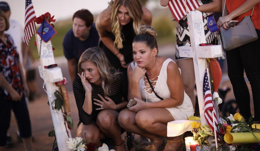 From left, Rachel Shepherd, Jamie Lambert and Annie Leach visit a makeshift memorial for victims of a mass shooting Friday, Oct. 6, 2017, in Las Vegas. Stephen Paddock opened fire on an outdoor country music concert on Sunday killing dozens and injuring hundreds. (AP Photo/John Locher) **FILE**
