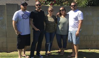 "In this Thursday, Oct. 5, 2017 photo, a group of friends that call themselves ""framily"" pose for a photo, from left, Casey Bodwell, Ryan Miller, Michelle Miller, Tracy Gyurina and Chad Elliot pose for a photo in Placentia, Calif. They all traveled with their friend Nicol Kimura to Las Vegas for the country western music festival. Kimura was killed in the shooting. (AP Photo/Amy Taxin)"