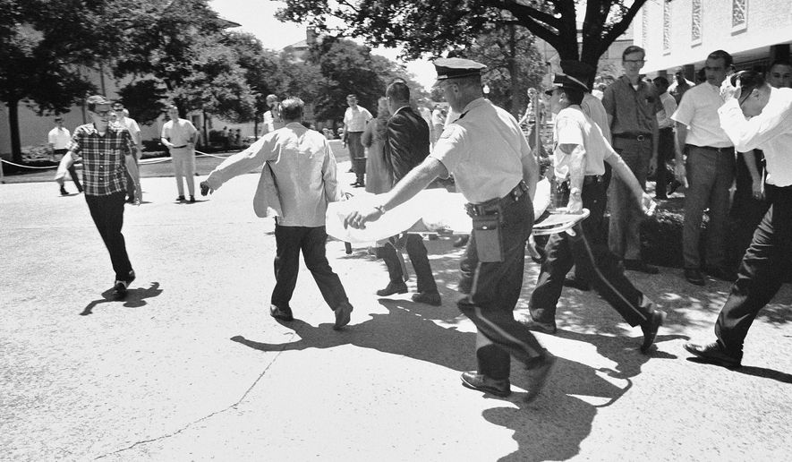 FILE - In this Aug. 1, 1966, file photo, one of the victims of Charles Joseph Whitman, the sniper who gunned down victims from a perch in the University of Texas tower, is carried across the campus to a waiting ambulance in Austin. Whitman, a 25-year-old architectural engineering major and ex-Marine, killed his wife, his mother and three others before climbing the 27 stories of a tower at the University of Texas and raining gunfire on the plaza below. Over 96 minutes, another 11 people were killed and 31 injured before Whitman was killed by police officers. (AP Photo/File)