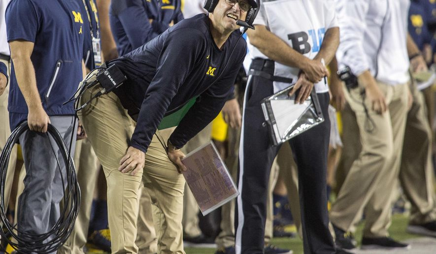 Michigan head coach Jim Harbaugh looks at the scoreboard along the sideline in the first quarter of an NCAA college football game against Michigan State in Ann Arbor, Mich., Saturday, Oct. 7, 2017. (AP Photo/Tony Ding)