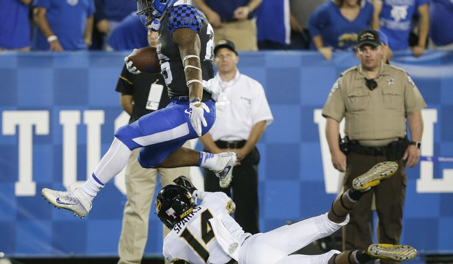 Kentucky running back Benny Snell Jr. jumps over Missouri defensive back Adam Sparks on his way to a touchdown during the first half of an NCAA college football game Saturday, Oct. 7, 2017, in Lexington, Ky. (AP Photo/David Stephenson)
