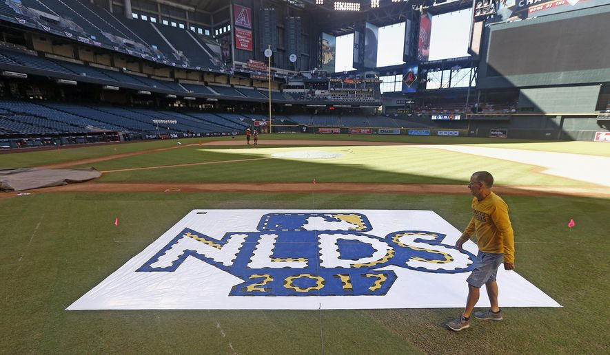 The grounds crew prepares the field before Game 3 of baseball's National League Division Series between the Arizona Diamondbacks and the Los Angeles Dodgers, Sunday, Oct. 8, 2017, in Phoenix. (AP Photo/Ross D. Franklin)