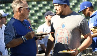 Chicago Cubs manager Joe Maddon, left, and Chicago Cubs' Kyle Schwarber, right, eat brunch during practice at Wrigley Field, Sunday, Oct. 8, 2017, in Chicago. Game 3 of the National League Division Series between the Washington Nationals and Cubs is Monday. (AP Photo/David Banks)