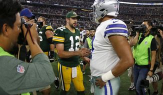 Green Bay Packers' Aaron Rodgers (12) and Dallas Cowboys' Dak Prescott (4) greet each other at midfield after their NFL football game, Sunday, Oct. 8, 2017, in Arlington, Texas. (AP Photo/Ron Jenkins)