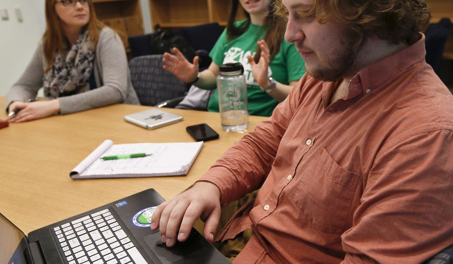 In this Tuesday, Feb. 7, 2017 photo, Penn State University student Jesse Weber, right, looks over his computer as fellow student Amber Morris, center, and program director Katie Tenney, left, exchange ideas during a Stand For State team meeting in State College, Pa. Penn State's Stand for State program is part of a large push in colleges across the country seeking to train people to be able to recognize, and step in, when a sexual assault is unfolding. (AP Photo/Keith Srakocic)