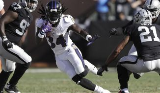 Baltimore Ravens running back Alex Collins (34) runs between Oakland Raiders defensive end Mario Edwards Jr. (97) and cornerback Sean Smith (21) during the second half of an NFL football game in Oakland, Calif., Sunday, Oct. 8, 2017. (AP Photo/Marcio Jose Sanchez)