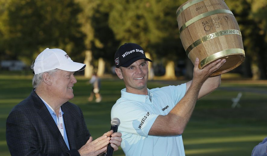 Brendan Steele holds up his trophy on the 18th green of the Silverado Resort North Course after winning the Safeway Open PGA golf tournament Sunday, Oct. 8, 2017, in Napa, Calif. Looking on at left is Hall of Famer Johnny Miller. (AP Photo/Eric Risberg)
