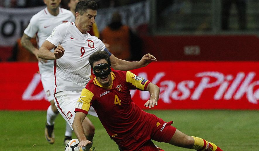 Poland's Robert Lewandowski, left, challenges Montenegro's Nikola Vukcevic, front, during the World Cup Group E qualifying soccer match between Poland and Montenegro at National stadium in Warsaw, Poland, Sunday, Oct. 8, 2017. (AP Photo/Czarek Sokolowski)