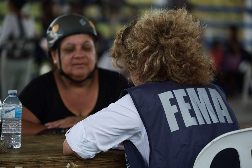 A resident meets with a FEMA representative to file forms for federal aid in the aftermath of Hurricane Maria at the Jose de Diego Elementary School in Las Piedras, Puerto Rico, Monday, Oct. 2, 2017. Power is still cut off on most of the island, schools and many businesses are closed and much of the countryside is struggling to find fresh water and food. (AP Photo/Carlos Giusti)