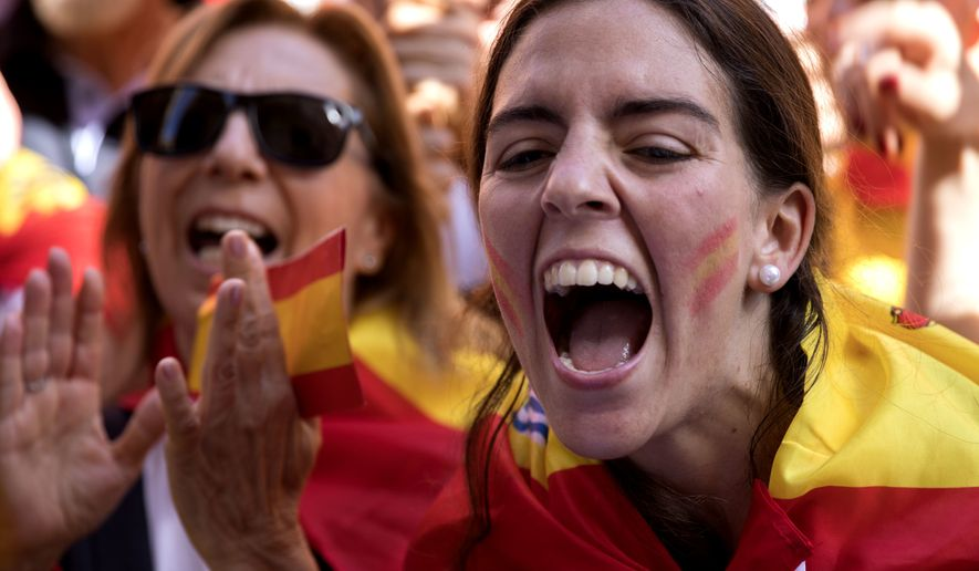 Demonstrators shout slogans as thousands of people march to protest the Catalan government's push for secession from the rest of Spain in downtown Barcelona, Spain, Sunday Oct. 8, 2017. Sunday's rally comes a week after separatist leaders of the Catalan government held a referendum on secession that Spain's top court had suspended and the Spanish government said was illegal.(AP Photo/Emilio Morenatti)