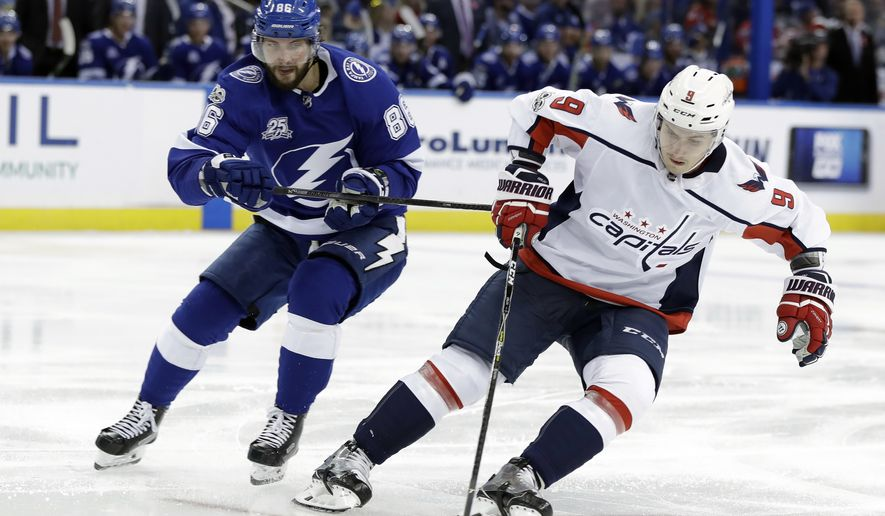 Washington Capitals defenseman Dmitry Orlov (9), of Russia, gets around Tampa Bay Lightning right wing Nikita Kucherov, also of Russia, during the second period of an NHL hockey game, Monday, Oct. 9, 2017, in Tampa, Fla. (AP Photo/Chris O'Meara)