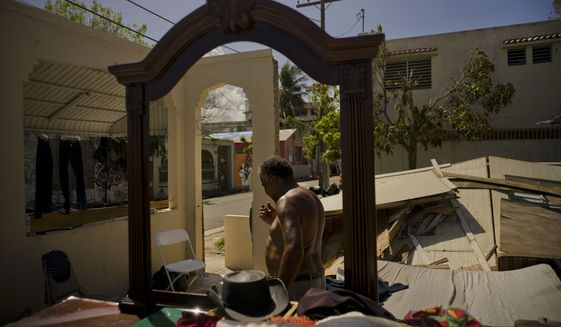 Efrain Diaz Figueroa walks around at the remains of the house of his sister destroyed by Hurricane Maria in San Juan, Puerto Rico, Monday, Oct. 9, 2017. Figueroa, who was visiting for a month at her sister Eneida's house when the Hurricane Maria hit the area, also lost her home in the Arroyo community. He waits for a relative to come from Boston and take him to Boston. He says that he is 70 years old and all his life working can't continue in these conditions in Puerto Rico. (AP Photo/Ramon Espinosa)