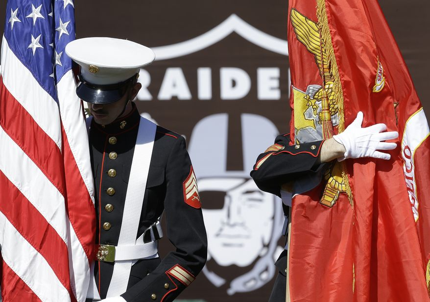 Military personnel hold flags before the performance of the national anthem before an NFL football game between the Oakland Raiders and the Baltimore Ravens in Oakland, Calif., Sunday, Oct. 8, 2017. (AP Photo/Ben Margot)