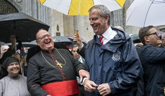 Archbishop of New York Cardinal Timothy Dolan, left, shares a light moment with New York Mayor Bill de Blasio during the annual Columbus Day Parade in New York Monday, Oct 9, 2017. (AP Photo/Craig Ruttle)