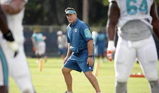 FILE - In this Aug. 16, 2016, file photo, Miami Dolphins offensive line coach Chris Foerster watches as players do drills during practice at NFL football training camp in Davie, Fla. The NFL and the Miami Dolphins say they're aware of a social media video allegedly showing offensive line coach Chris Foerster snorting a white powdery substance. NFL spokesman Brian McCarthy said Monday, Oct. 9, 2017, the league will review the 56-second video, which was posted on Facebook and Twitter. (AP Photo/Lynne Sladky, File)
