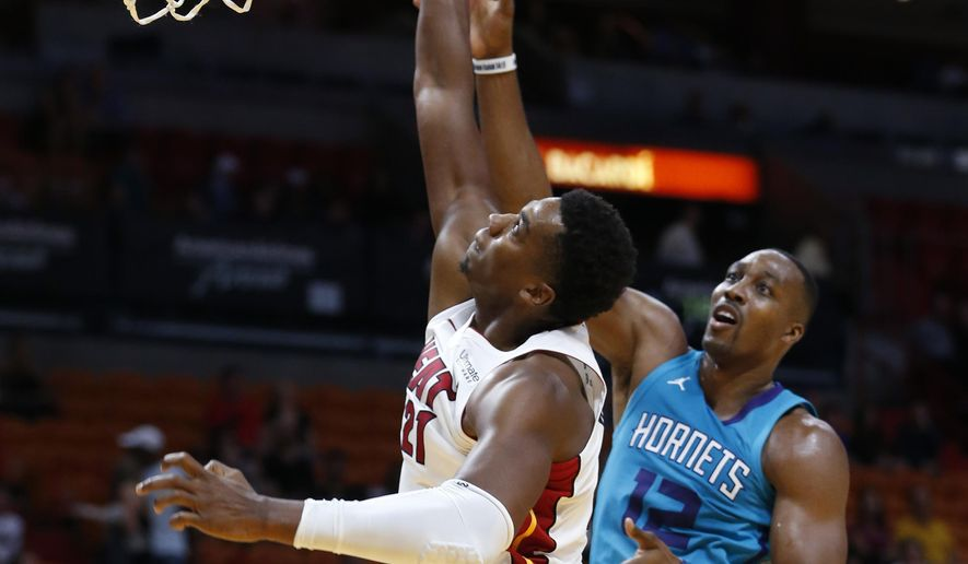 Miami Heat center Hassan Whiteside (21) blocks a shot from Charlotte Hornets center Dwight Howard (12) during the first half of an NBA preseason basketball game, Monday, Oct. 9, 2017, in Miami. (AP Photo/Wilfredo Lee)