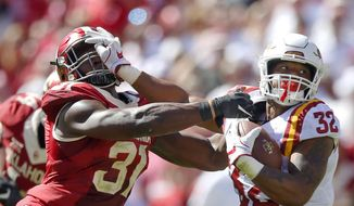 Iowa State running back David Montgomery (32) stiff arms Oklahoma defensive end Ogbonnia Okoronkwo (31) during an NCAA college football game in Norman, Okla., Saturday, Oct. 7, 2017. Iowa State defeated No. 3 Oklohoma 38-31. (Ian Maule/Tulsa World via AP)