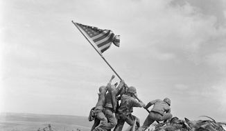 FILE - In this Feb 23, 1945 file photo, U.S. Marines of the 28th Regiment, 5th Division, raise the American flag atop Mt. Suribachi, Iwo Jima, Japan. On Monday, Oct. 9, 2017, which would have been Joe Rosenthal's 106th birthday, a group will deliver their petition with over 2,000 signatures and a letter requesting a future USS Joe Rosenthal to Secretary of the Navy Richard V. Spencer, who is responsible for naming ships. (AP Photo/Joe Rosenthal)