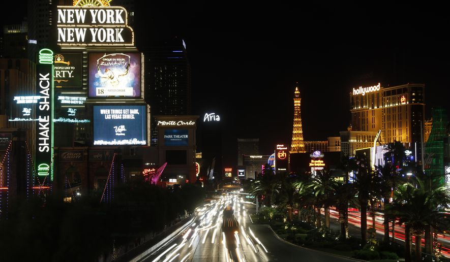 Some of the casinos along the Las Vegas Strip dim their marquees signs for about 10 minutes Sunday, Oct. 8, 2017, in Las Vegas, to pay tribute to the victims who spent that much time under fire in the Las Vegas shooting on Sunday, Oct. 1. (AP Photo/Steve Marcus)