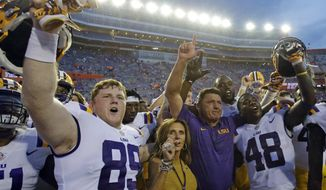 LSU wide receiver Jonathan Giles (89) and linebacker Donnie Alexander (48) celebrate victory over Florida 17-16 with LSU head coach Ed Orgeron, second from right, and his wife Kelly Oregon after an NCAA college football game, Saturday, Oct. 7, 2017, in Gainesville, Fla. (AP Photo/John Raoux)