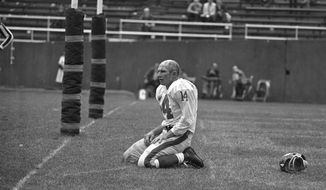 FILE - In this Sept. 20, 1964, file photo, New York Giants' Y.A. Tittle squats on the field after being hit hard while passing during a game against the Pittsburgh Steelers, in Pittsburgh. Tittle, the Hall of Fame quarterback and 1963 NFL Most Valuable Player, has died. He was 90. His family confirmed to LSU, where Tittle starred in college, that he passed away. No details were immediately provided. (AP Photo/Dozier Mobley, File)