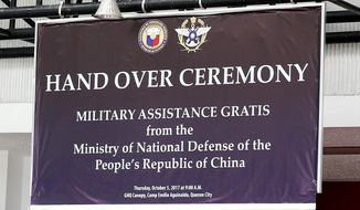 "In this Oct. 5, 2017 photo, a tarpaulin, showing the logo of the Philippine Defense Department, top left, and that of Taiwan's Ministry of Defense, top right, is hung from the canopy of the General Headquarters of the Armed Forces of the Philippines for the turnover ceremony of hundreds of Chinese-made assault rifles by China to the Philippines at Camp Aguinaldo in suburban Quezon city, northeast of Manila, Philippines. On Monday, Oct. 9, 2017, the Philippines' defense department has apologized to China for the ""grievous but purely unintentional mistake"" of using Taiwan's defense ministry logo during a ceremony where the Chinese ambassador turned over assault rifles to the Filipino defense chief and top military commanders. (AP Photo/Bullit Marquez)"