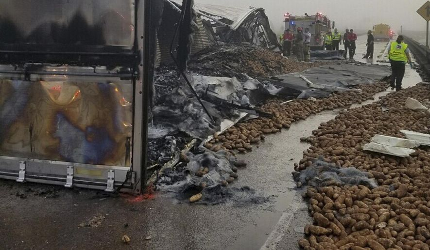In this image provided by the Louisiana State Police, potatoes lie on Interstate 10 near Butte La Rose, La., on Monday, Oct. 9, 2017. A trucker died in the wreck that engulfed a tractor-trailer in flames and left thousands of potatoes scattered across the interstate. (Louisiana State Police via AP)