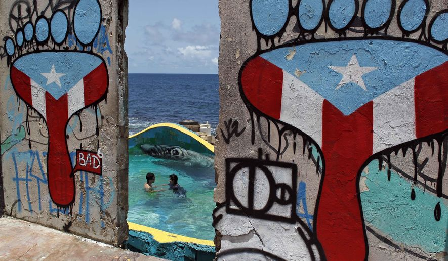 "This Aug. 25, 2017 photo shows a couple swimming, framed by a concrete wall blanketed with graffiti, in the seaside slum La Perla, in San Juan, Puerto Rico. La Perla is suddenly a popular tourism spot thanks in part to this year's hit song ""Despacito,"" whose video became the most-watched in YouTube history. (AP Photo/Ricardo Arduengo)"