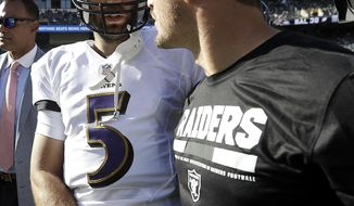 Baltimore Ravens quarterback Joe Flacco (5) greets injured Oakland Raiders quarterback Derek Carr after an NFL football game in Oakland, Calif., Sunday, Oct. 8, 2017. The Ravens won 30-17. (AP Photo/Marcio Jose Sanchez)
