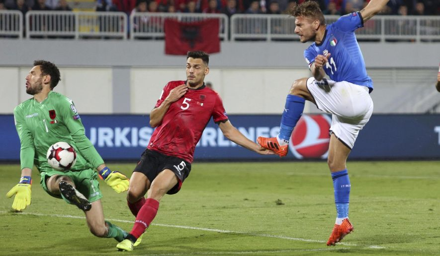 Albania's goalkeeper Etrit Berisha, left, saves a shot by Italy's Ciro Immobile, right, as Albania's Frederic Veseli looks on during the World Cup Group G qualifying soccer match between Albania and Italy at Loro Borici stadium, in Shkoder, northern Albania, Monday, Oct. 9, 2017. (AP Photo/Hektor Pustina)