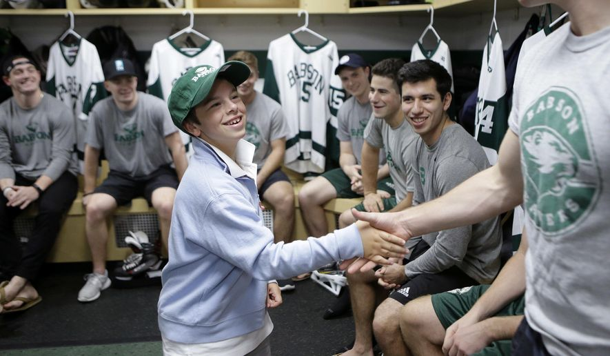Coleman Walsh, 10, of Walpole, Mass., center, greets members of the Babson College men's ice hockey team after signing an official letter of intent during ceremonies, Tuesday, Oct. 10, 2017, in Wellesley, Mass., to induct him to the team. Since birth, Coleman has been fighting Williams syndrome, a developmental disorder that affects numerous parts of the body. The induction was organized by Team IMPACT, a national nonprofit that connects colleges with youngsters dealing with debilitating or life-threatening illness. (AP Photo/Steven Senne)