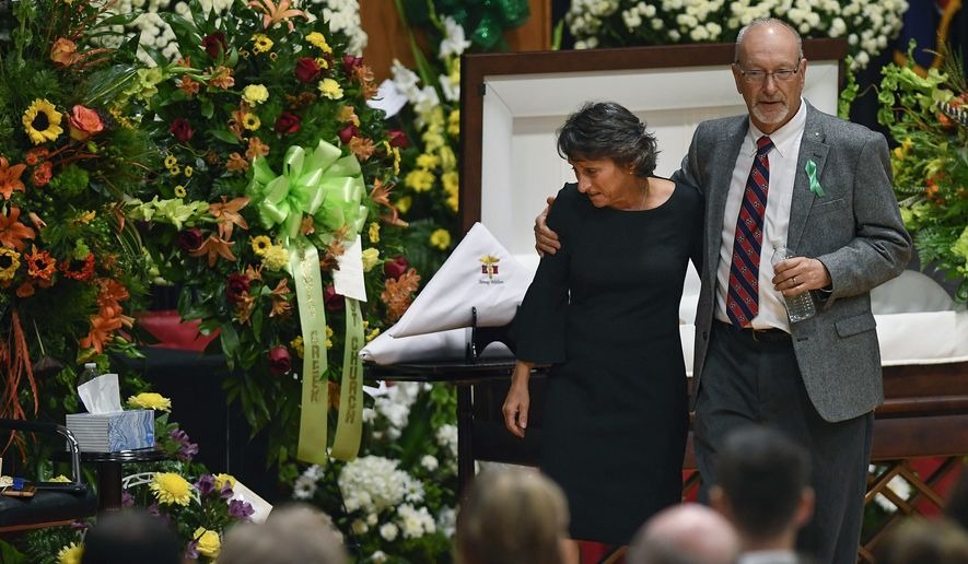 Susan Melton is comforted by James Warren Melton as she takes her seat before her son Sonny Melton's funeral at Big Sandy High School, Tuesday, Oct. 10, 2017,  in Big Sandy, Tenn. Melton, a registered nurse, died protecting his wife during the Las Vegas shooting massacre.  (Morgan Timms /The Jackson Sun via AP)