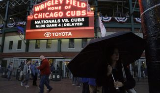 Fans leave Wrigley Field after Game 4 of baseball's National League Division Series between the Chicago Cubs and the Washington Nationals was postponed until Wednesday due to rain, Tuesday, Oct. 10, 2017, in Chicago. (AP Photo/Nam Y. Huh)
