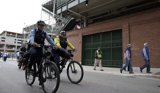 Police patrol the street outside Wrigley Field before Game 4 of baseball's National League Division Series between the Chicago Cubs and the Washington Nationals, Tuesday, Oct. 10, 2017, in Chicago. (AP Photo/Nam Y. Huh)