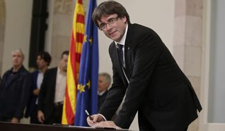 "Catalan regional President Carles Puigdemont signed an independence declaration after a parliamentary session in Barcelona, Spain, on Tuesday. Mr. Puigdemont says he has a mandate to declare independence for the northeastern region but proposes waiting ""a few weeks"" in order to facilitate a dialogue. (Associated Press)"