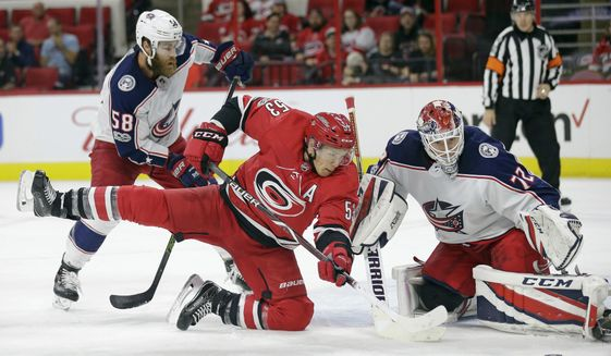 Carolina Hurricanes' Jeff Skinner (53) tries to score while Columbus Blue Jackets goalie Sergei Bobrovsky (72), of Russia, defends with Blue Jackets David Savard (58) during the second period of an NHL hockey game in Raleigh, N.C., Tuesday, Oct. 10, 2017. (AP Photo/Gerry Broome)