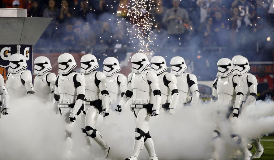 "Stormtroopers march down the field during the halftime of an NFL football game between the Chicago Bears and the Minnesota Vikings, Monday, Oct. 9, 2017, in Chicago. The trailer for ""Star Wars: The Last Jedi"" debuted in dramatic fashion during Monday Night Football halftime. Fireworks flashed and Stormtroopers marched onto Chicago's Soldier Field as the preview played onscreen. (AP Photo/Charles Rex Arbogast)"