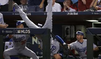 Los Angeles Dodgers' Cody Bellinger falls in the dugout after catching a foul ball by Arizona Diamondbacks' Jeff Mathis during the fifth inning of game 3 of baseball's National League Division Series, Monday, Oct. 9, 2017, in Phoenix. (AP Photo/Rick Scuteri)