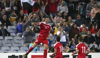 Syria's Omar Al Somah, left, jumps up after scoring against Australia during their Soccer World Cup qualifying match in Sydney, Australia, Tuesday, Oct. 10, 2017. (AP Photo/Rick Rycroft)