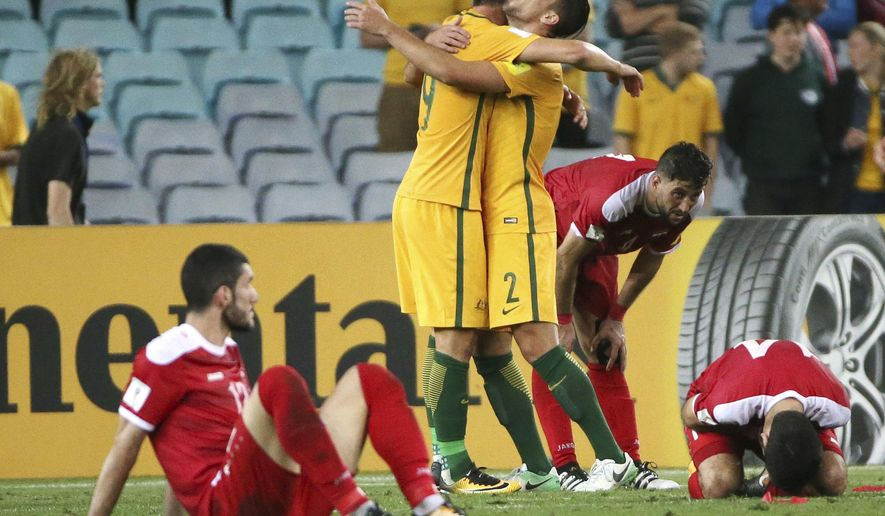 Australia's Tomi Juric, center left, and Milos Degenek celebrates their win over Syria in their Soccer World Cup qualifying match in Sydney, Australia, Tuesday, Oct. 10, 2017. (AP Photo/Rick Rycroft)