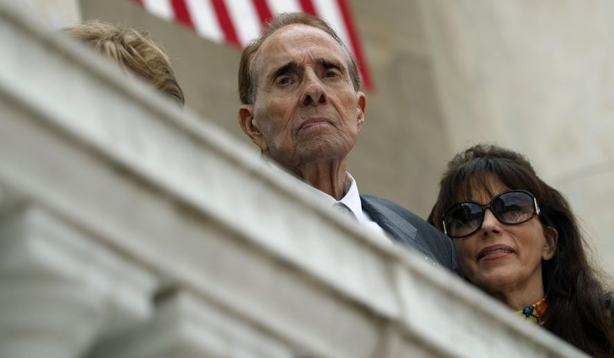 FILE - In this May 29, 2017 file photo former Republican presidential candidate and U.S. Senate Majority Leader Sen. Bob Dole watches as President Donald Trump speaks during a Memorial Day ceremony at Arlington National Cemetery, in Arlington, Va. Dole has returned home after being hospitalized for three weeks with low blood pressure. Dole spokeswoman Marion Watkins said in an email Tuesday, Oct. 10 that the 94-year-old former Kansas senator was discharged Thursday, Oct. 5 from the Walter Reed National Military Medical Center outside Washington, D.C.  (AP Photo/Evan Vucci, File)